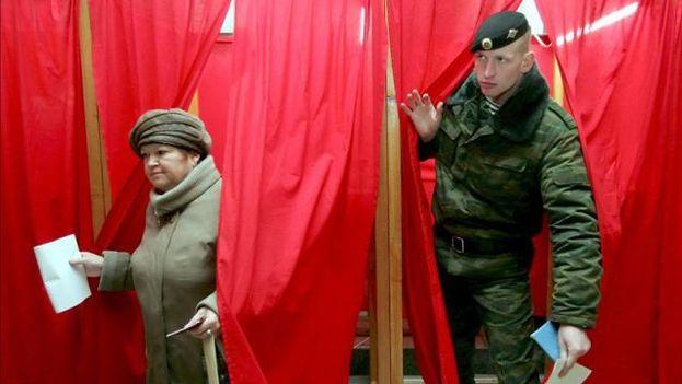 Una mujer y un militar ruso se disponen a votar en unas elecciones rusas. (EFE)