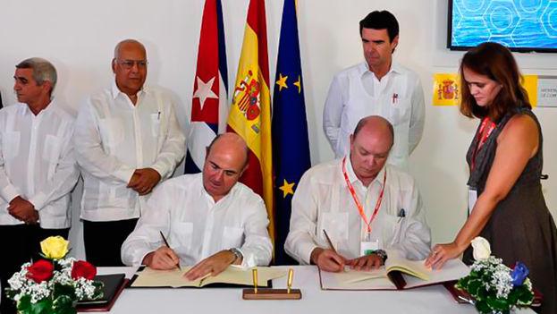 El ministro de Economía y Competitividad, Luis de Guindos (izq.), y el ministro cubano de Comercio Exterior e Inversión Extranjera, Rodrigo Malmierca (der), firman acuerdos de cooperación en La Habana en presencia del ex ministro de Energía y Turismo, José Manuel Soria (de pie). (EFE)