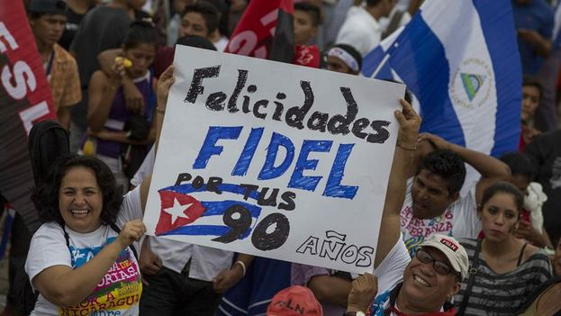 Una pareja levanta una pancarta con la que felicita a Fidel Castro por sus próximos 90 años. (EFE/Jorge Torres)
