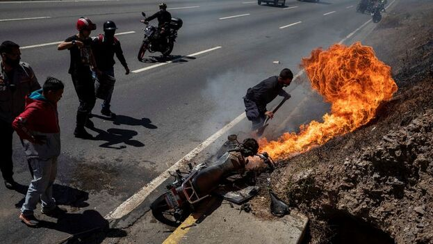 Los paramédicos llegan al sitio del suceso y un hombre yace sobre la basura y el agua sucia de una cuneta de la autopista que conecta Caracas con el costero estado de La Guiara. (EFE)