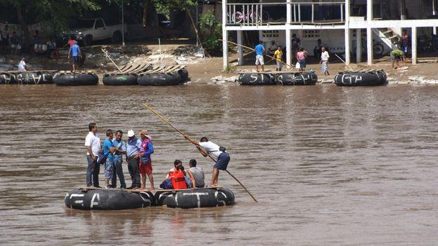 Un grupo de personas cruza a bordo de una balsa desde Guatemala en dirección al lado mexicano. (Manu Ureste)