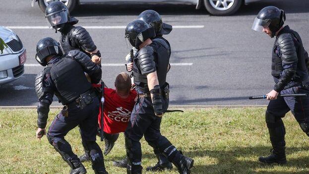 La policía se lleva detenido a un hombre que intentó poner flores donde murió uno de los manifestantes en Minsk. (EFE)