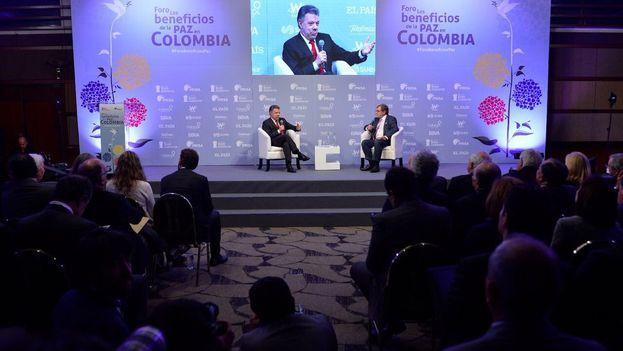 El presidente de Colombia, Juan Manuel Santos, conversa con el presidente del grupo Prisa, Juan Luis Cebrián en el foro sobre beneficios de la paz en Colombia. (@JuanManSantos)