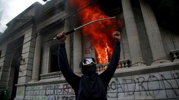 Un hombre protesta frente al Congreso de Guatemala mientras este arde en llamas. (EFE/Esteban Biba)