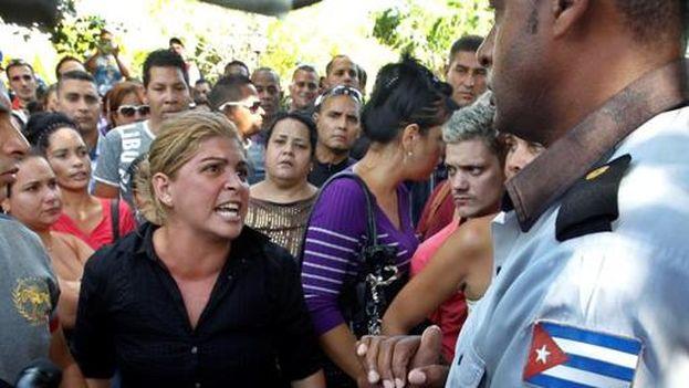 Una mujer protesta frente a la embajada de Ecuador en La Habana. (EFE)