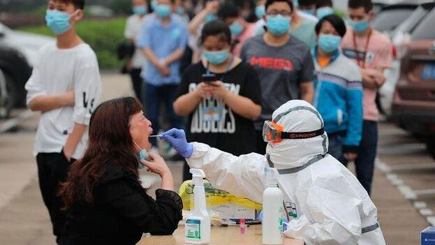 Un sanitario realizando test de coronavirus a la población de Wuhan, el pasado mes de mayo. (EFE/EPA/Li Ke/Archivo)