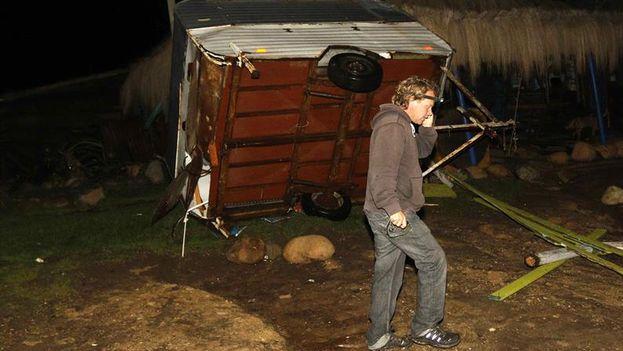 Un hombre pasa frente a un remolque volcado por una ola , en la localidad de Con Con, cerca de Valparaíso. (Raul Zamora/EFE)