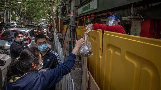 Un vendedor entrega una compra de comida a un cliente a través de las barreras de separación entre una calle y un área residencial en Wuhan. (EFE/EPA/ROMAN PILIPEY)