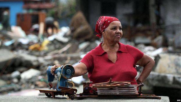 Una mujer sostiene su máquina de coser en medio de la desolación dejada por Matthew en Baracoa. (EFE)