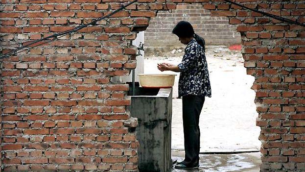 Una mujer se lava las manos en un gueto ocupado por trabajadores emigrantes, en Pekín (Foto Michael Reynolds/EFE)