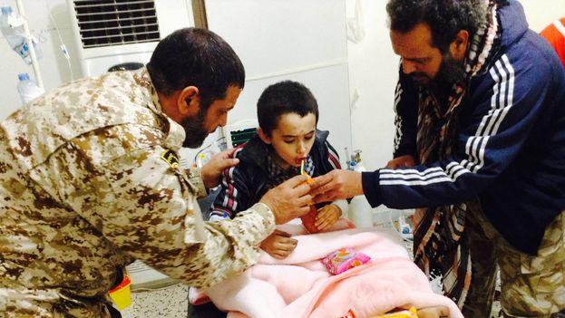 Un menor desnutrido es alimentado por dos uniformados en Sirte, tras la retirada y derrota del ISIS en la ciudad libia. (FAHMI IGWIAAN)