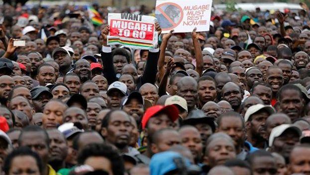 """Los zimbabuenses llevan pancartas con mensajes como """"Mugabe, vete ya"""" o """"Zimbabue no es una empresa privada, Mugabe debe dimitir"""". (EFE)"""