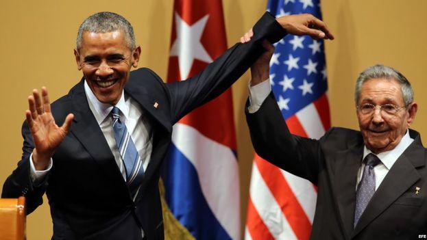 El gobernante cubano Raúl Castro trata de levantar el brazo del presidente de EEUU, Barack Obama, después de una conferencia de prensa en La Habana. (EFE)