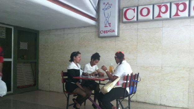 Las empleadas de la heladería Coppelia, en la ciudad de Camagüey, almuerzan tranquilas a las afueras del local, que no recibe suministro del producto desde que se paralizó la industria. (14ymedio)