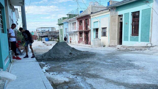 La calle San Luis está llena de materiales de la construcción, en la acera unos jóvenes escuchan música a todo volumen mientras los constructores van y vienen en su faena. (14ymedio)