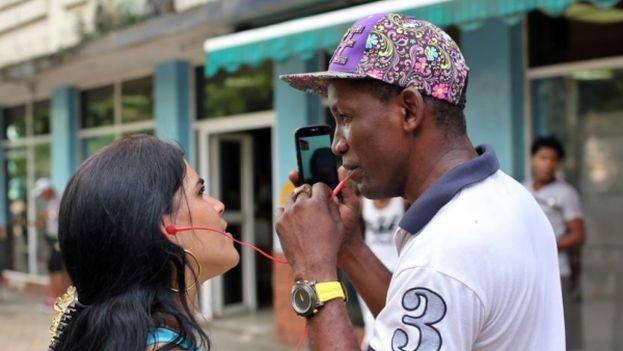 Cubanos efectuando una videollamada en una punto Wi-fi (EFE)