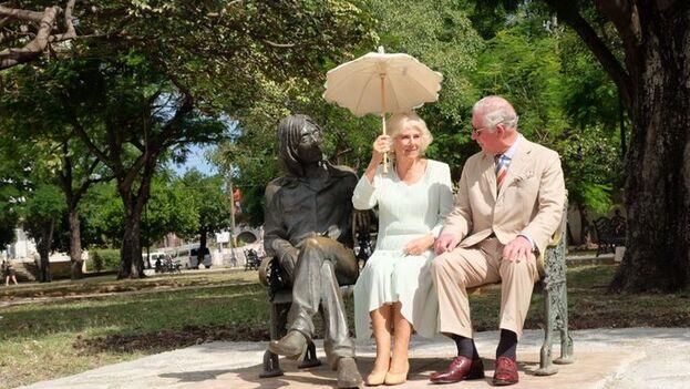 El príncipe de Gales y la duquesa de Cornualles sentados en el banco junto a la efigie de Lennon. (Clarencehouse)
