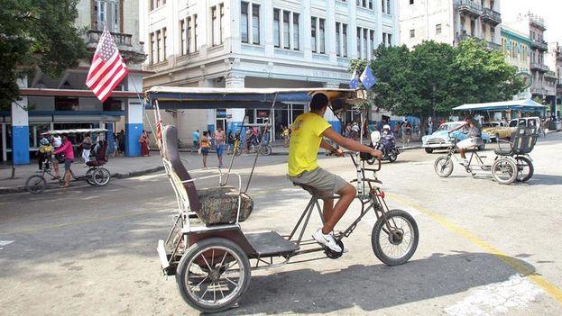 Un bicitaxi luce una bandera estadounidense por las calles de La Habana un día después del encuentro entre Obama y Castro. (EFE/Ernesto Mastrascusa)