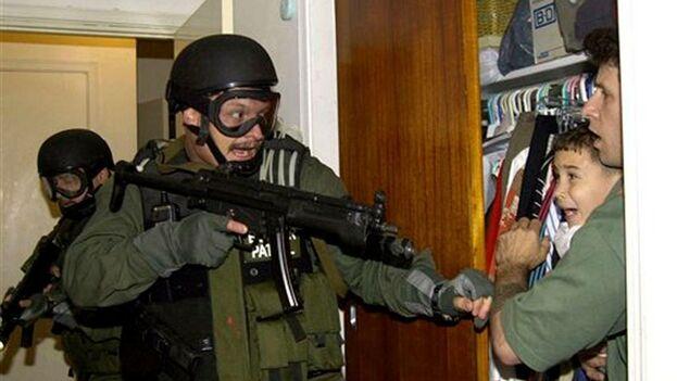 En esta icónica foto, Donato Dalrymple protege a Elián en un closet, de los agentes federales que registraban la casa de su familia en la Pequeña Habana, el 22 de abril del 2000. (Archivo)