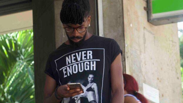 Joven cubano con un teléfono