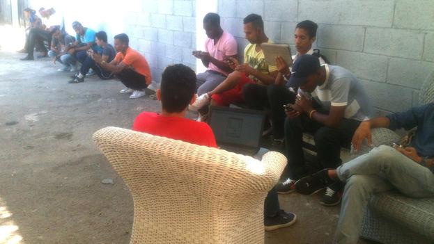Jóvenes sentados en loa alrededores del Kcho Estudio Romerillo para hacer uso de la red WIFI (14ymedio)