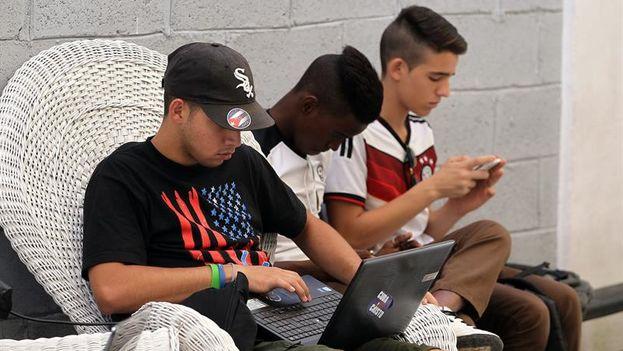Jóvenes cubanos intentan acceder a una red wifi del Museo Orgánico de Romerillo. (EFE)