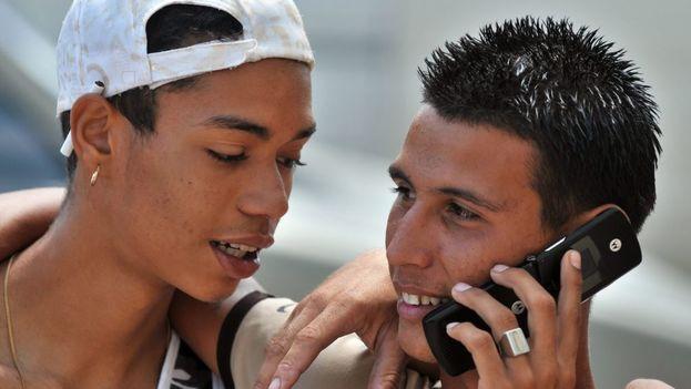 Jóvenes cubanos conversan telefónicamente a través de un celular. (EFE)