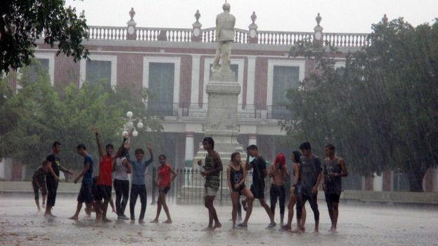 Jóvenes holguineros celebran la llegada de la lluvia en el céntrico parque Calixto García (Donate)