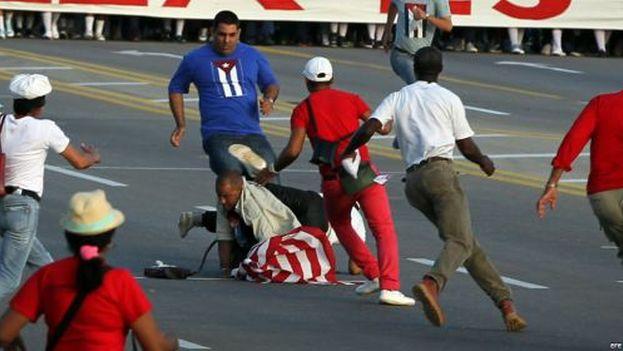Llorente fue reducido durante la marcha del 1 de Mayo cuando irrumpió en el desfile con la bandera estadounidense. (Captura)