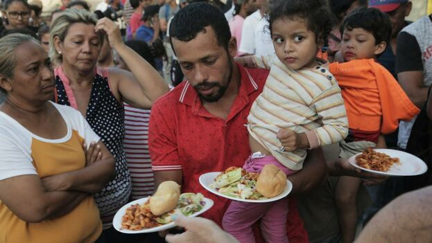 Un padre emigrante y su hija reciben comida en un campamento ubicado en Matamoros, México, a la entrada del Puente Internacional Gateway que conecta la ciudad de Matamoros con Brownsville, en Texas. (el Nuevo Herald)