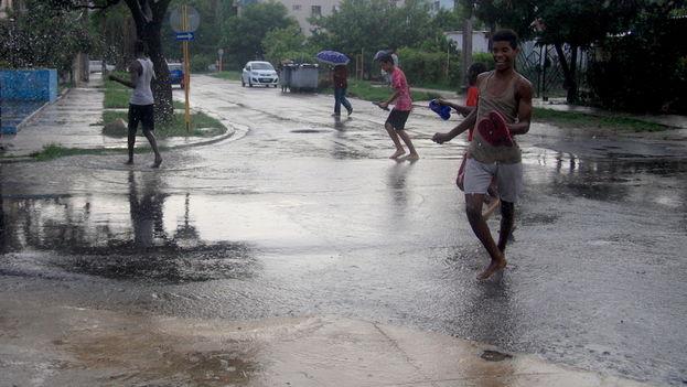Muchachos bañándose bajo la lluvia en La Habana. (14ymedio)