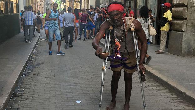 Un hombre muestra una imagen de San Lázaro en la céntrica calle Obispo de La Habana Vieja. (14ymedio)