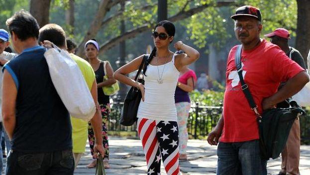 Una mujer ataviada con la bandera de Estados Unidos en La Habana mientras espera la guagua en el Parque de la Fraternidad. (EFE)