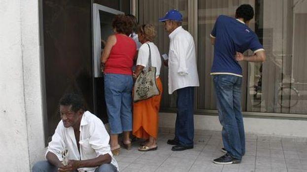 Varias personas hacen fila ante un cajero electrónico en Santa Clara. (EFE)