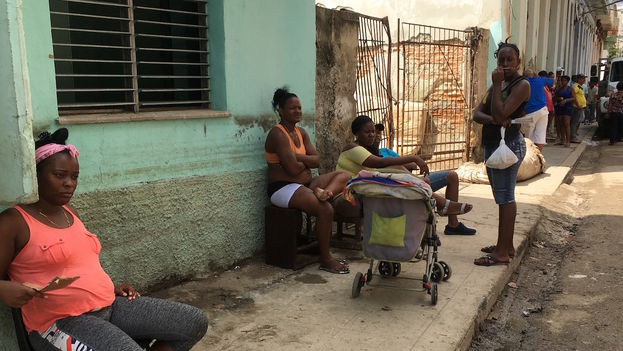 Vecinos de calle Ánimas refrescan en la acera el intenso calor ante la fatla de electricidad. (14ymedio)