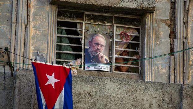 Una mujer se asoma por la ventana de un apartamento en La Habana en noviembre del 2016. (el Nuevo Herald)
