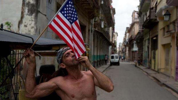 Un cubano besa una bandera norteamericana en una calle de La Habana Vieja. (EFE)