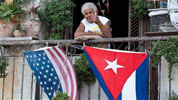 Una señora desde su balcón saluda con las banderas de Cuba y Estados Unidos ondeando hacia afuera. (EFE)
