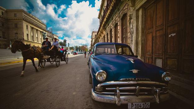 En las cercanías del capitolio de La Habana unos turistas pasean en un coche de caballos. (flickr)