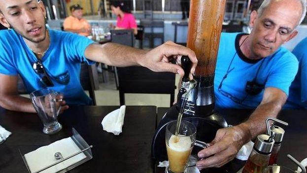 Dos hombres sirven cerveza de barril en una fábrica del producto en La Habana. (EFE)