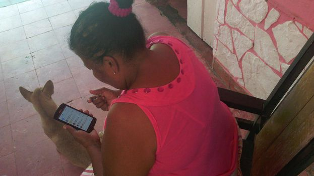 Una mujer se conecta a internet a través de una red informal que capta desde el portal de su casa en la ciudad de Camagüey. (14ymedio)