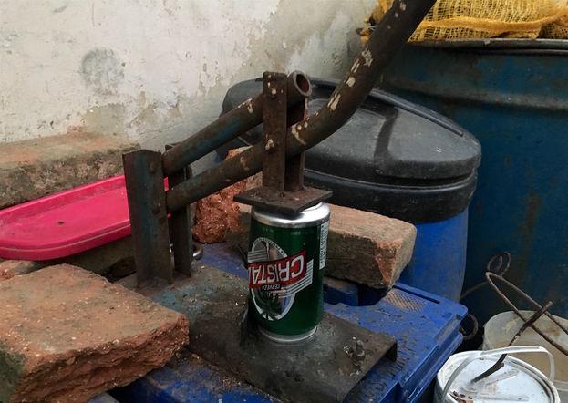 En el patio de su casa ha creado una herramienta para escachar las latas que recoge por las calles. (14ymedio)
