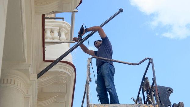 """Un empleado dando """"los últimos ajustes"""" en la fachada del Hotel Manzana Kempinski, en La Habana. (14ymedio)"""