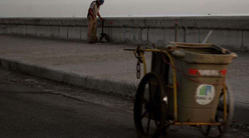 Un empleado de servicios comunales limpia junto al muro del malecón habanero