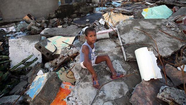 Un niño sentado en los escombros tras el paso del huracán Matthew en Baracoa, Guantánamo. (EFE/Archivo)