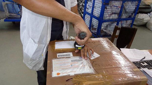 Una funcionaria inspecciona un paquete enviado a la Isla. (Correos de Cuba)