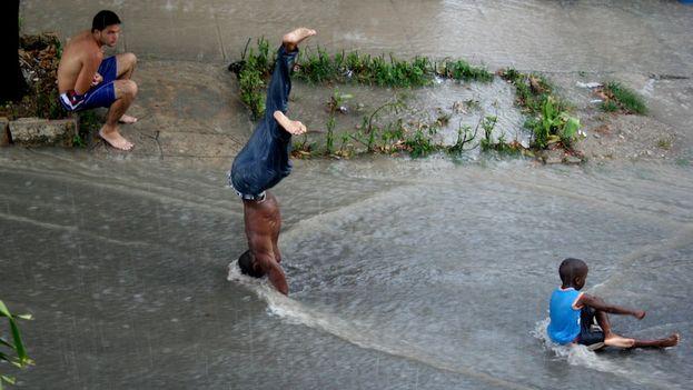 Un grupo de niños juega bajo la lluvia. (14ymedio)