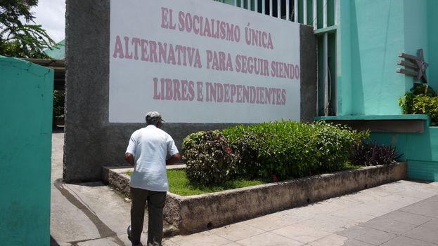 Un hombre camino junto a una valla política en La Habana. (14ymedio)