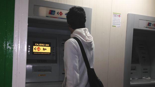 Un joven saca dinero en un cajero automático cubano