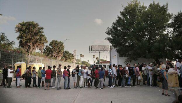 Los migrantes hacen fila para comer en un campamento ubicado en el lado de Matamoros, México, del Puente Internacional que conecta Matamoros con Brownsville, Texas. La iglesia y las organizaciones voluntarias en Brownsville llevan el agua y los alimentos para los migrantes en el lado mexicano de la frontera mientras esperan que se procesen sus solicitudes de asilo. (el Nuevo Herald).
